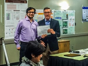 Xavi Fonoll of the University of Michigan accepts the award for top poster in physical modeling group  from Bob Johns, a senior fellow at the Humphrey School of Public Affairs and strategy adviser to the network.