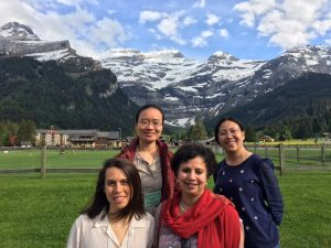 SHCN researchers pose for a group photo at the 2018 GRC on Industrial Ecology, swiss alps in the backgroud. Clockwise: SHCN post-doctoral researcher Lin Zeng, SHCN director Anu Ramaswami, SHCN post-doctoral researcher Dana Boyer, and SHCN post-doctoral researcher Kangkang Tong.