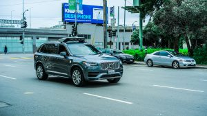 A self-driving Volvo SUV operated by Uber driving on the street.