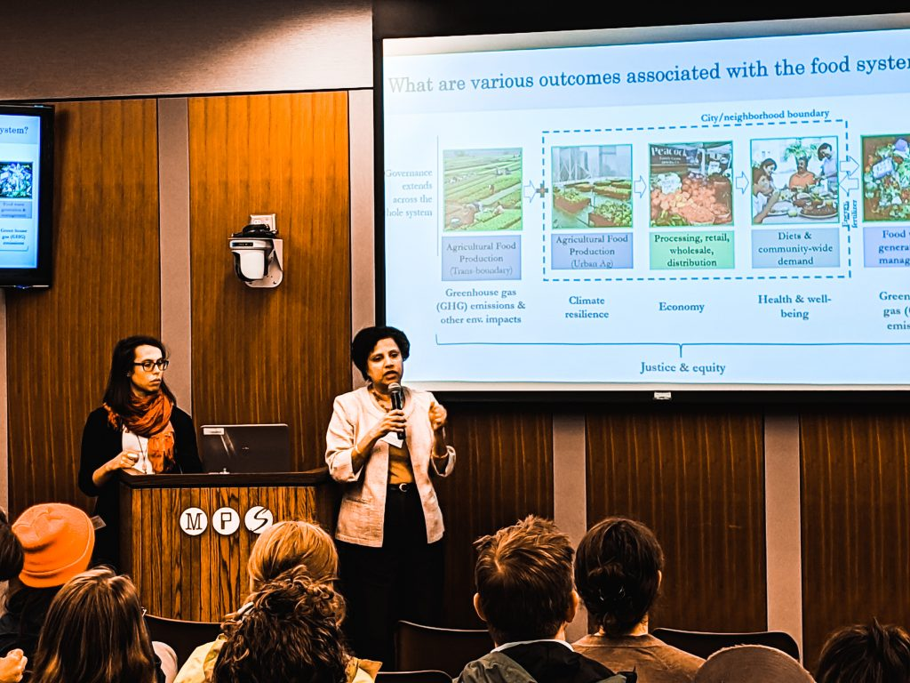 Two researchers present research to a community forum audience.